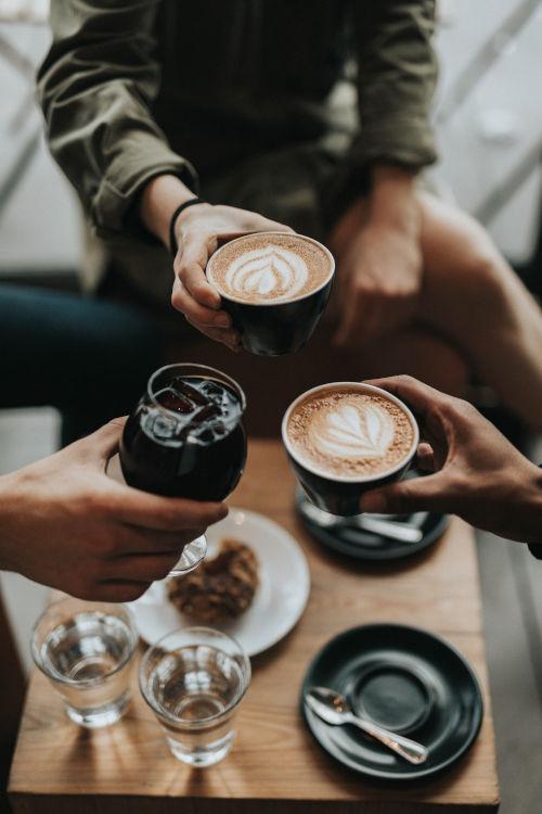 Bild von Freunden im Café die mit Getränken anstoßen